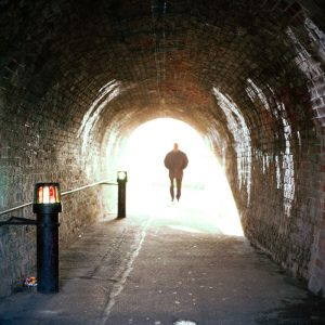 Man walking through tunnel